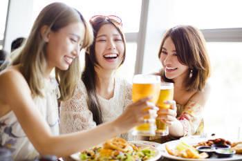3人の女子が料理を前に乾杯をしている