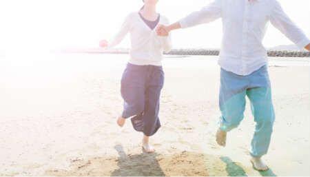 砂浜を走る男女の画像