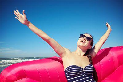 海辺で空を仰ぐサングラスの女性