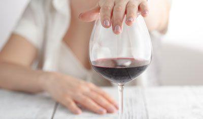 ワイングラスの口を手で塞ぐ女性