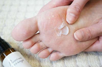 足の裏にクリームを塗っている