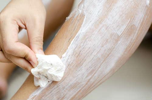 脚に塗ったクリームをティッシュで拭っている