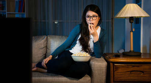 女性が夜遅くにポップコーンを食べている