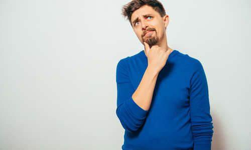 首を傾げる中年男性