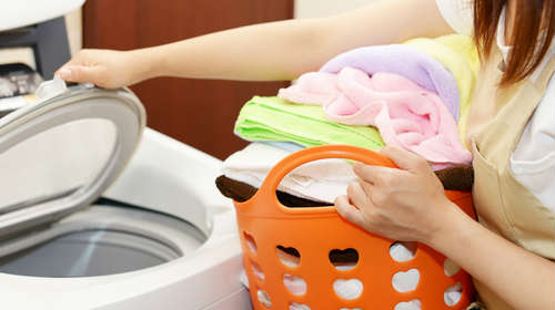 洗濯物を持った女性が洗濯機を開けている