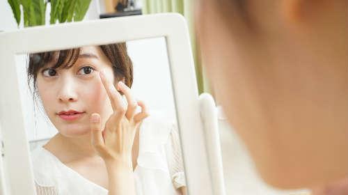 鏡に映る顔を覗き込んでいる女性