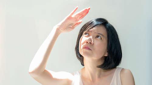 日差しにかざした手で影をつくる女性