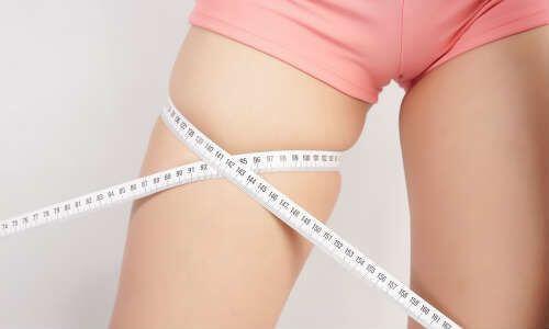 太ももをメジャーで測っている女性