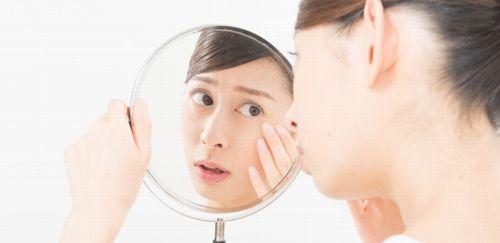 女性が鏡で目尻をチェックしている