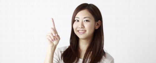 人差し指を立てている笑顔の女性
